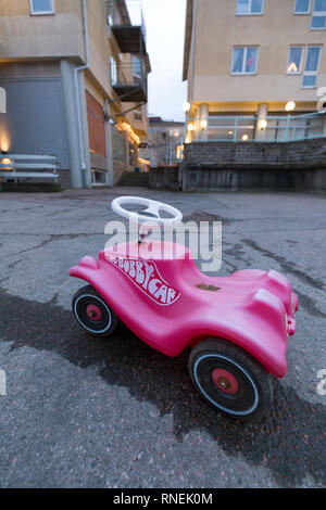 Pink Big Bobby Car left behind outside on the street - Stock Image