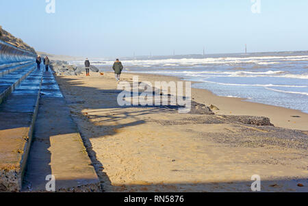 A view westwards with beach walkers along the shoreline at high water on the Norfolk coast at Sea Palling, Norfolk, England, United Kingdom, Europe. - Stock Image