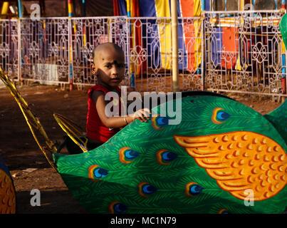 Girl child India enjoying peacock ride in children park at Odisha India - Stock Image