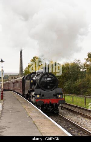 Standard class 4 steam engine 80080 hauling its train into Rawtenstall station on the East Lancashire Railway. - Stock Image