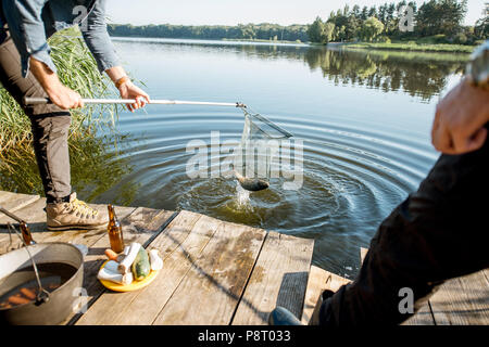 Fisherman catching big fish with fishing net on the lake in the morning - Stock Image