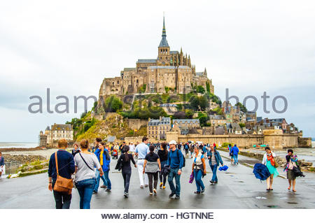 Visitors on the walkway approach to Mont St Michel on a cloudy & wet day in Normandy, France. - Stock Image