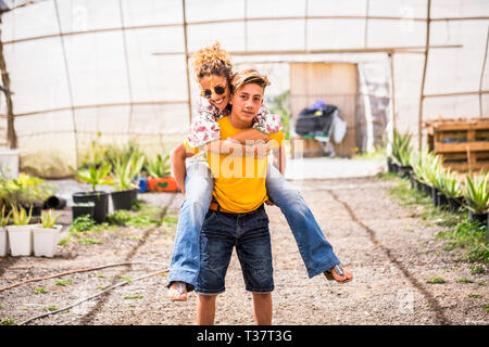 young beautiful teenager play with his mother middle age pretty woman carrying her to his back. couple mother son having fun together like a perfect f - Stock Image