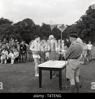 1960s, historical, a young male scout in his athletic shorts receiving a certificate infront of parents and other children. - Stock Image