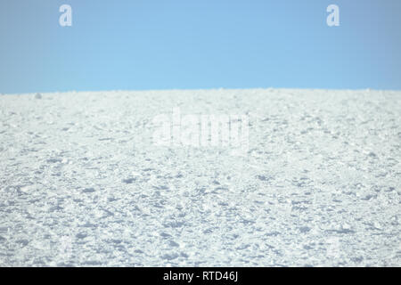Compacted fresh snow against blue sky. Sunny day. Background with copy space for text. Winter time - Stock Image