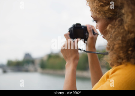African woman taking photograph - Stock Image