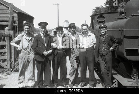 1950s, group photo of a railway station master, railway workers, train driver and train staff standing on a platform by a steam locomotive, England, UK. - Stock Image