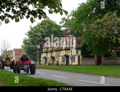 George and Dragon public house in Sutton Courtenay, Oxfordshire. Two tractors drive past. - Stock Image
