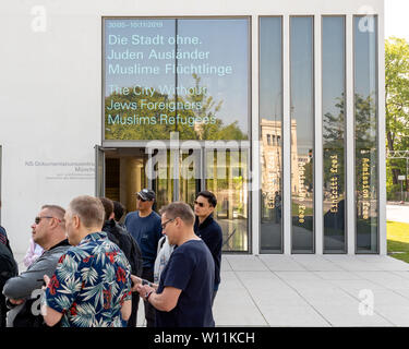 Munich, Bavaria, Germany - May 18, 2019. Tourists lisent to a presentation at the entrance of N-S documentation center for the history of national soc - Stock Image