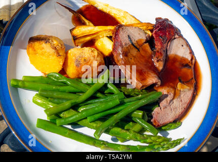 Easter Day English lunch  dinner meal roast lamb roast potatoes green beans parsnips and red wine gravy on a blue edged white plate on  outdoor table - Stock Image