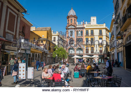 People eating outside at cafes in Plaza del Pan in Seville - Stock Image
