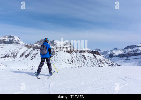 Young skier standing at the edge of a mountain range in Lake Louise looking at the Canadian Rockies of Alberta, Canada. - Stock Image