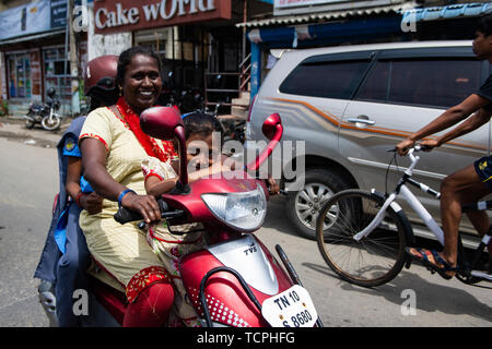 A family smile to the camera from their scooter in Chennai, India - Stock Image