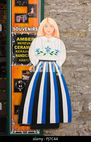 Estonia traditional costume, view of a female display figure outside a Tallinn souvenir shop wearing a costume in the colours of the national flag. - Stock Image