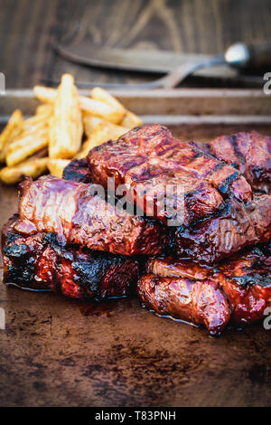 Bbq boneless beef ribs with barbecue sauce and potato wedges over a rustic background. Extreme shallow depth of field with blurred background and sele - Stock Image