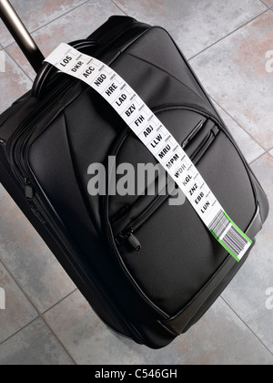 A suitcase with a long luggage tag indicating a frequent flyer - Stock Image