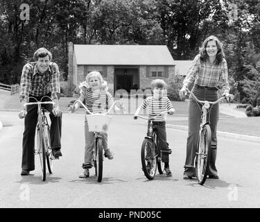 1970s SUBURBAN FAMILY OF FOUR SITTING ON BICYCLES LOOKING AT CAMERA - b25779 HAR001 HARS NOSTALGIC ACTIVE 4 SUBURBAN MOTHERS OLD TIME NOSTALGIA BROTHER OLD FASHION SISTER FITNESS JUVENILE STYLE HEALTHY TEAMWORK SONS PLEASED FAMILIES JOY LIFESTYLE FEMALES STRIPED MARRIED BROTHERS BIKING SPOUSE HUSBANDS HEALTHINESS HOME LIFE FULL-LENGTH PHYSICAL FITNESS DAUGHTERS MALES PLAID SIBLINGS CONFIDENCE BICYCLES SISTERS TRANSPORTATION FATHERS B&W BIKES EYE CONTACT FREEDOM WIDE ANGLE ACTIVITY HAPPINESS PHYSICAL WELLNESS CHEERFUL LEISURE STRENGTH DADS PRIDE OF ON SIBLING SMILES CONNECTION FLEXIBILITY - Stock Image