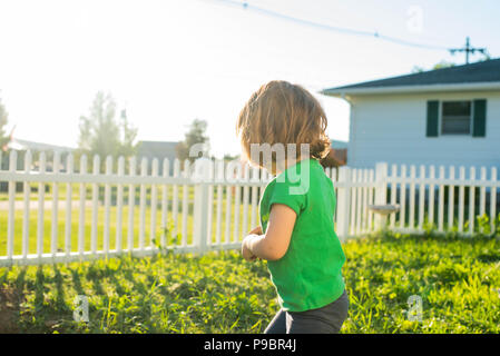 A toddler girl plays in the dirt late in the afternoon in the summer. - Stock Image