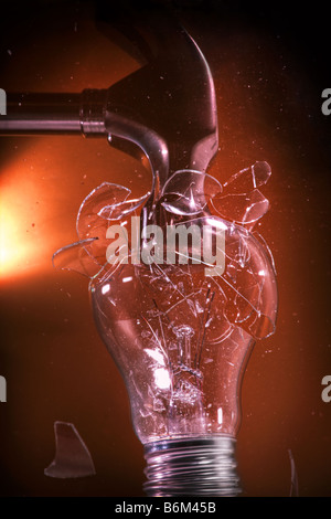 Conventional incandescent light bulb crushed by hammer - Stock Image