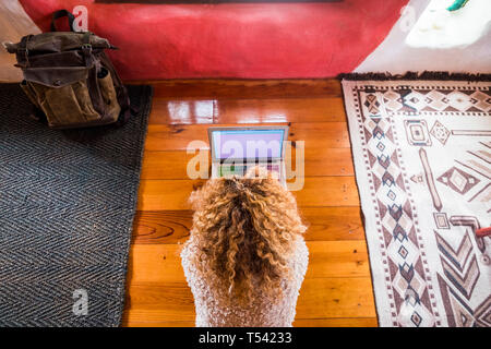 Curly blonde woman working at the laptop lay down on the floor in hotel or home room viewed from above - lady using computer notebook during travel in - Stock Image