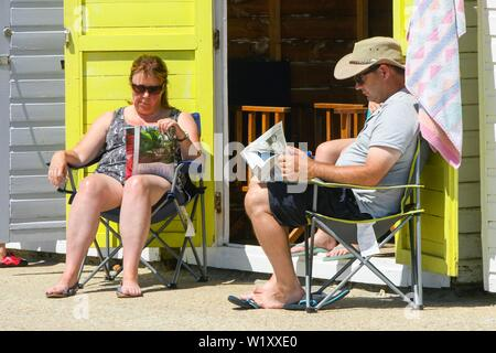 Lyme Regis, Dorset, UK.  4th July 2019. UK Weather.  A couple reading outside a seafront beach hut at the seaside resort of Lyme Regis in Dorset enjoying a day of clear skies and scorching hot sunshine.   Picture Credit: Graham Hunt/Alamy Live News - Stock Image