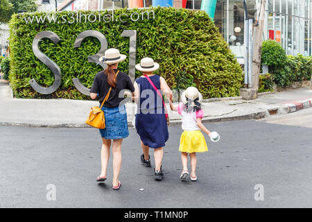 Bangkok, Thailand - 23rd March 2018: 3 generations crossing the road wearing hats. The city is very popular with tourists. - Stock Image