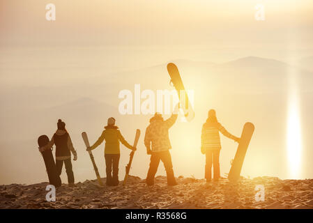 Group of skiers and snowboarders at sunset. Ski resort concept - Stock Image