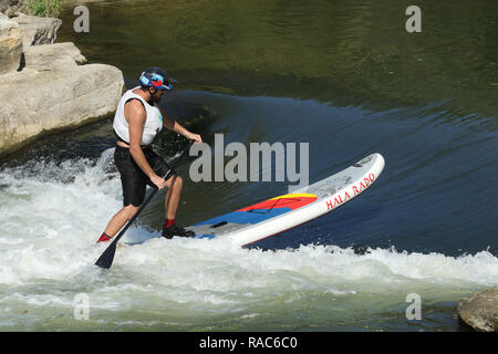 Standup Paddleboarder rides in a water trough. At the Whitewater feature in the Mad River. Wagner Subaru Outdoor Experience at Eastwood Metro Park, Fi - Stock Image