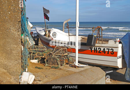 A small inshore fishing boat with equipment beached above the seawall on the North Norfolk coast at West Runton, Norfolk, England, UK, Europe. - Stock Image