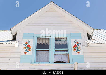 An old Norwegian style home with painted rosemaling shutters in the tiny village of Petersburg on Mitkof Island, Alaska. Petersburg settled by Norwegian immigrant Peter Buschmann is known as Little Norway due to the high percentage of people of Scandinavian origin. - Stock Image