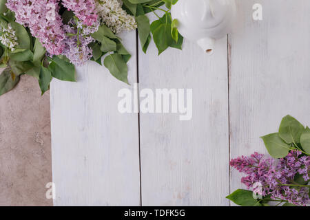 The decor of the flowers on the background of painted white wooden boards. Vintage background with lilac flowers and a place under the text. View from - Stock Image