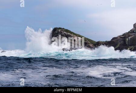 Waves breaking over rocky coast in Ilhabela, SP - Brazil - Stock Image