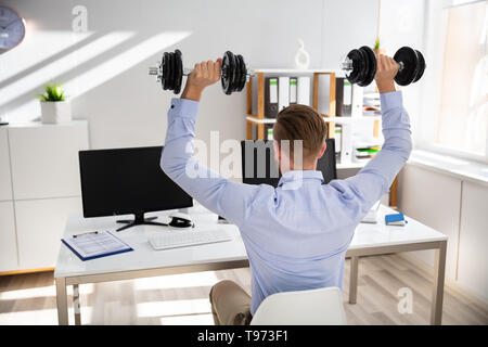 Attractive Businessman Exercising With Dumbbells In Office - Stock Image