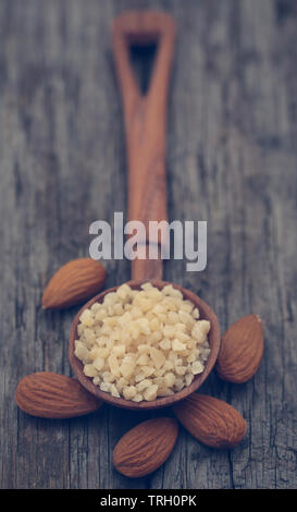 Small pieces of chopped almonds in wooden scoop with whole ones - Stock Image