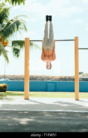 Beautiful young man training and working out in park. Handsome hispanic male athlete exercising with an abdomen routine for wellness. Latino people do - Stock Image