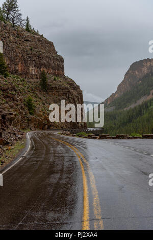 Wet Road Curves Around Rock Cliff in Canyon - Stock Image