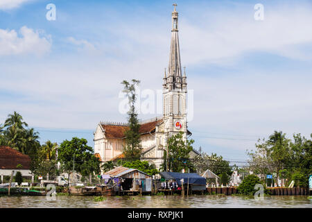 20th century Catholic Cathedral Church behind typical tin shack stilt houses on riverside of Co Chien River in Mekong Delta. Cai Be, Vietnam - Stock Image