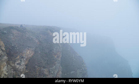 Two females in the distance having a picnic on top the cliffs above the coast, with sea mist swirling around obscuring the view. - Stock Image