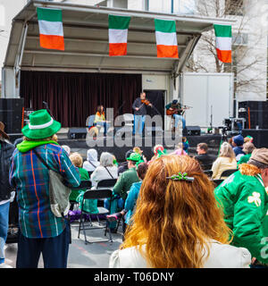 CHARLOTTE, NC, USA-3/16/19: A red-haired woman stands and listens to an Irish music band on St. Patrick's Day in uptown Charlotte. - Stock Image