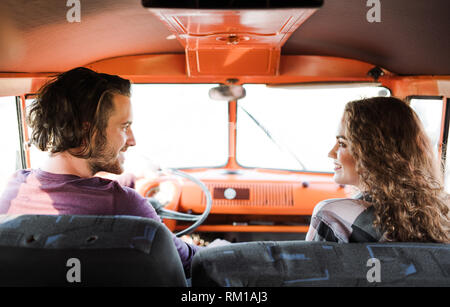 A rear view of young couple on a roadtrip through countryside, driving minivan. - Stock Image