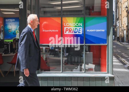 London, UK. 21st June, 2019. A pedestrian walks past a travel agent shop front in Soho decorated with rainbow flags in preparation for the annual Pride celebration and LGBT equality and tolerance Credit: amer ghazzal/Alamy Live News - Stock Image