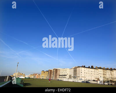 The vapour trails of three planes form a star shaped with their Contrails over Hove lawns on Brighton and Hove seafront. - Stock Image