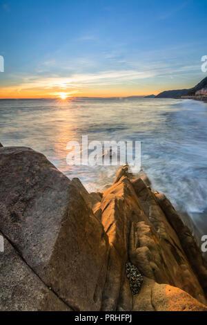 Sunset in Italy by the sea coast Italian Riviera Ligure Liguria Cinque Terre La Spezia Cinqueterre beach blue sky landscape seascape view rocks Autumn - Stock Image