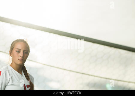 Low angle view of focused athlete standing in soccer goal under sunny sky - Stock Image