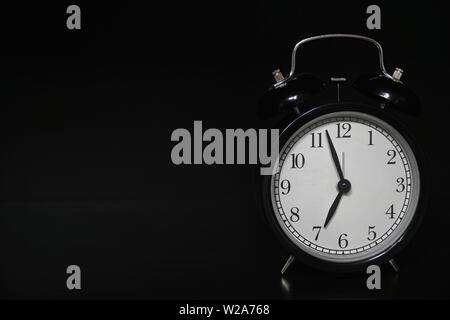 Classic mechanical alarm clock on dark background - Stock Image
