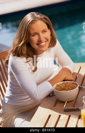Girl having breakfast by pool - Stock Image