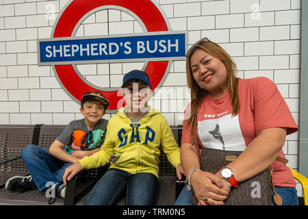A Mum and her sons sit on a bench at Shepherd's Bush London Underground station and wait for a train. - Stock Image