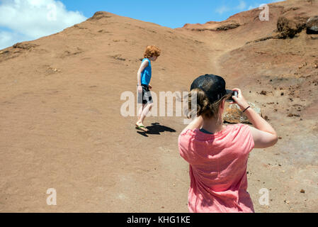 Girl taking picture of a boy in a park - Stock Image