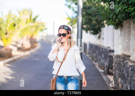Hippy people portrait with attractive blonde middle age woman walking and calling at the phone on the street in outdoor leisure activity - happy peopl - Stock Image