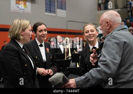 MURFREESBORO, Tenn. (March 16, 2019) Members of the flute section speak with a member of the audience during intermission at the Navy Band concert at Blackman High School in Murfreesboro, Tennessee. The U.S. Navy Band performed in 10 states during its 23-city, 5,000-mile tour, connecting communities across the nation to their Navy. - Stock Image